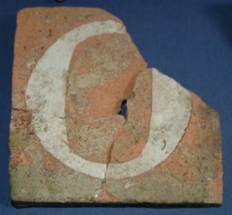 Fragment of 13th century floor tile showing the letter 'O' possibly from a high grade inscription. Probably made in the Exeter area