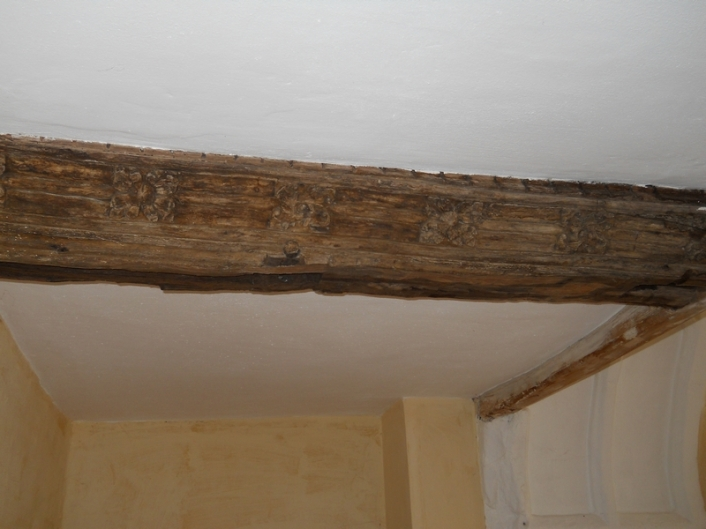 Newly exposed section of carved painted head beam
